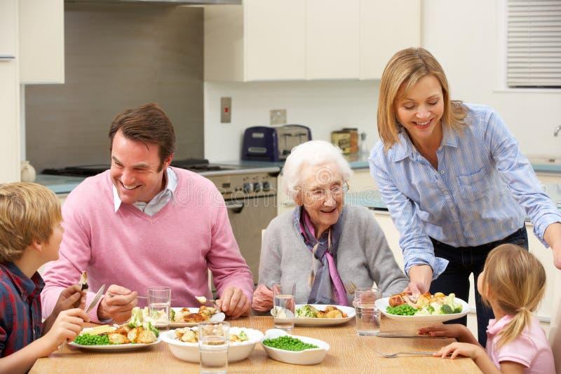 Von mehreren Generationen Familie, die zusammen Mahlzeit teilt stockfotografie