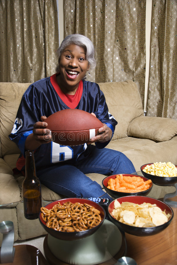 Von mittlerem Alter African-Americanfrau, die einen Fußball anhält. stockfotografie