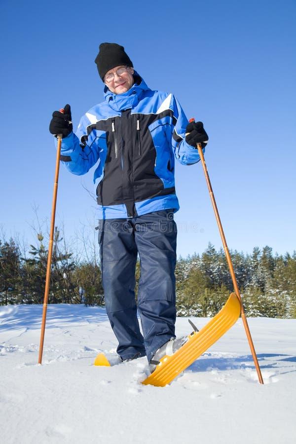 Von mittlerem Alter Mann, der auf Skis lächelt stockfotos