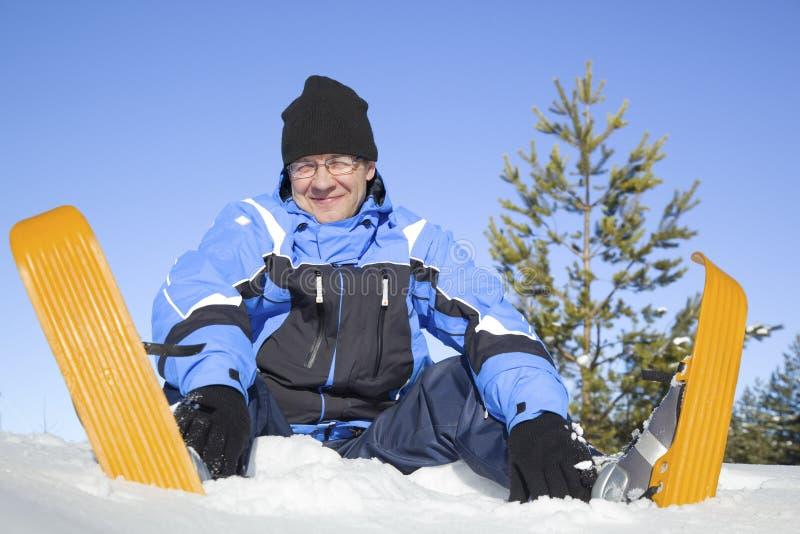 Von mittlerem Alter Mann, der im Schnee sitzt stockfotografie