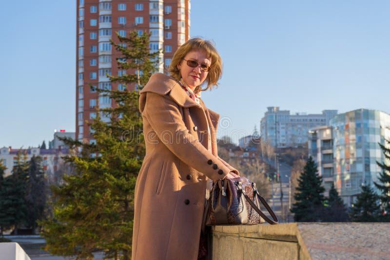 Von mittlerem Alter tragender modischer Mantel der attraktiven Frau, der um Stadt im Vorfrühling bei Sonnenuntergang geht Straßen stockfoto