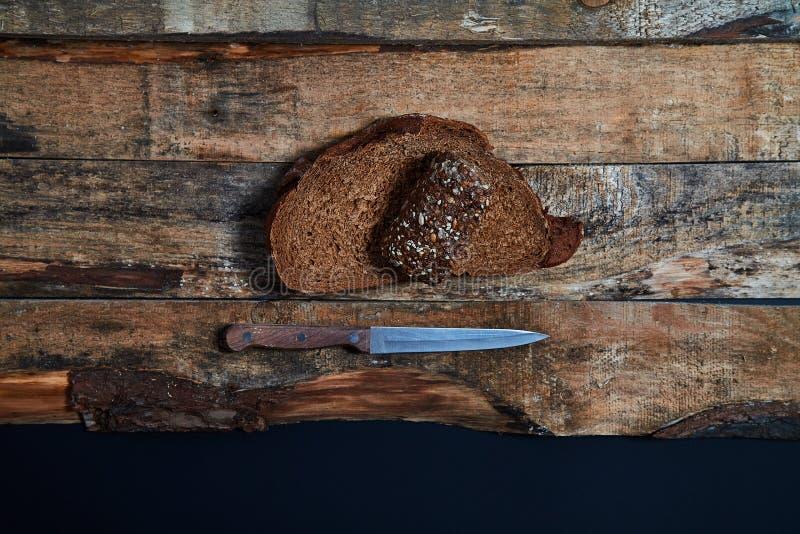 Von oben von geschnittenem Getreidebrot mit Messer auf rustikalen hölzernen Planken auf schwarzem Hintergrund stockfotografie