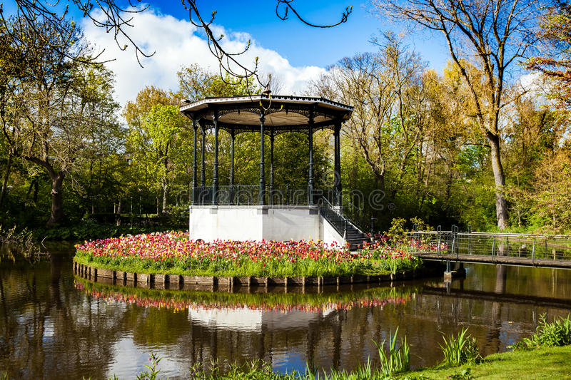 Vondelpark in Amsterdam, Netherlands. Pond with beautiful rotunda arc and tulips in Vondelpark in Amsterdam, Netherlands stock photos