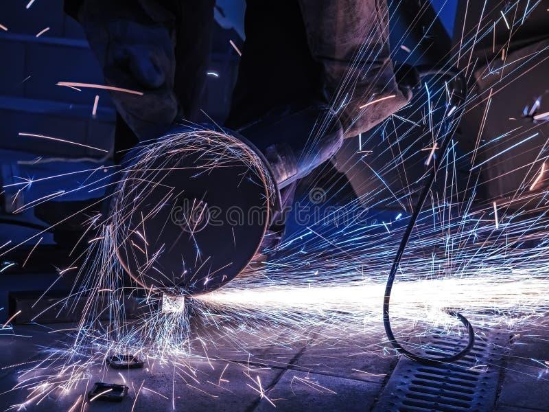 Vonken tijdens knipsel van de molen van de metaalhoek Heel wat gloeiende vonken vliegt rond de roterende schijf van de molen stock foto