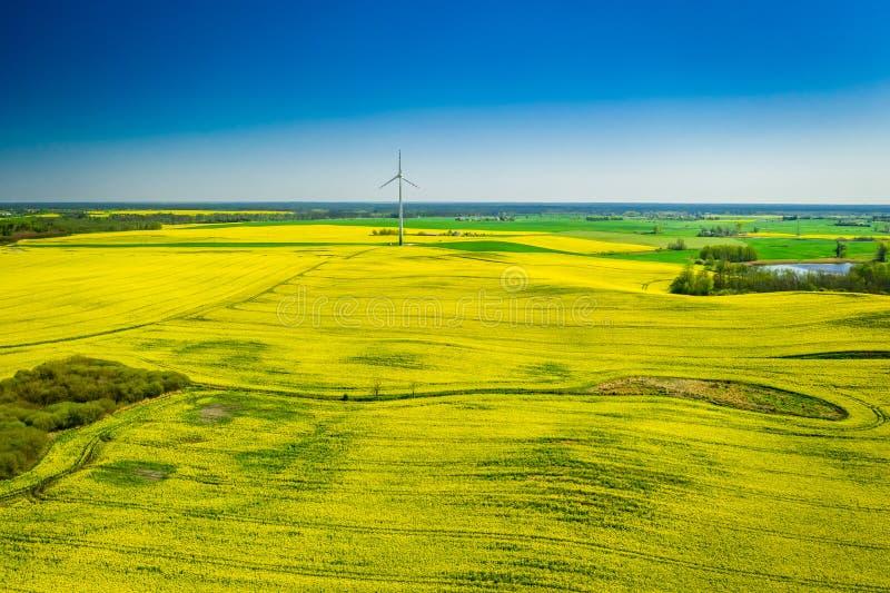 Voo acima dos campos e da turbina eólica verdes da violação no Polônia fotos de stock