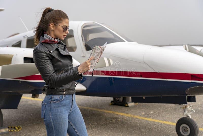 Voo bonito de Reading Map Before do piloto da jovem mulher fotos de stock royalty free