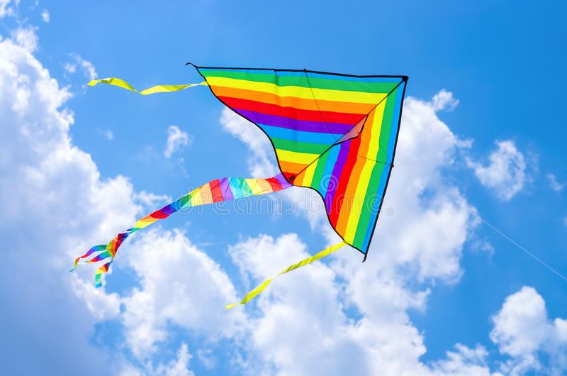 Voo colorido do papagaio do voo no céu foto de stock