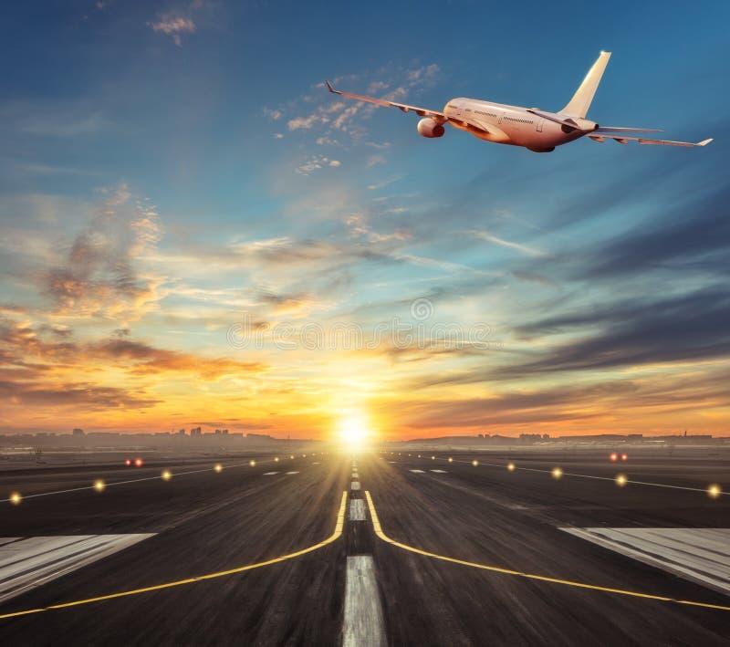 Voo comercial do avião acima da pista de decolagem na luz do por do sol fotografia de stock