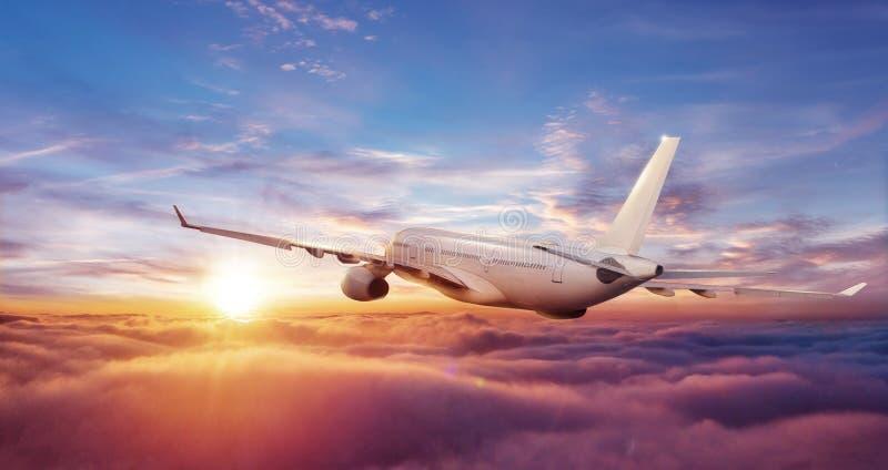 Voo comercial grande do avião acima das nuvens no por do sol imagem de stock royalty free