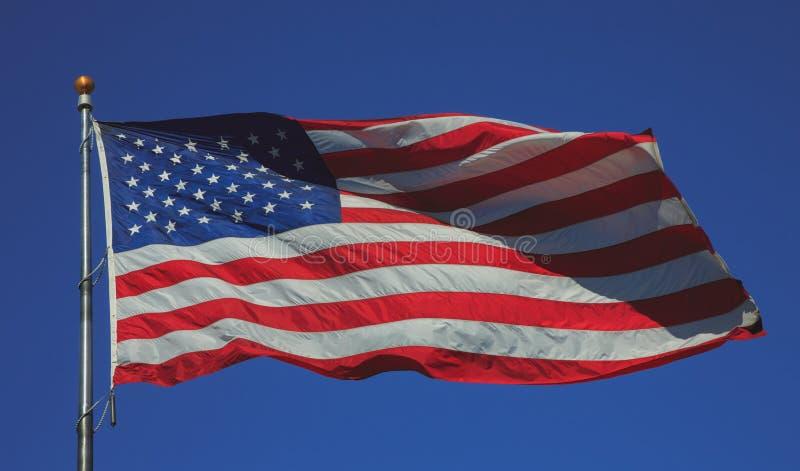 Voo da bandeira dos E.U. no forte vento em um céu azul imagem de stock