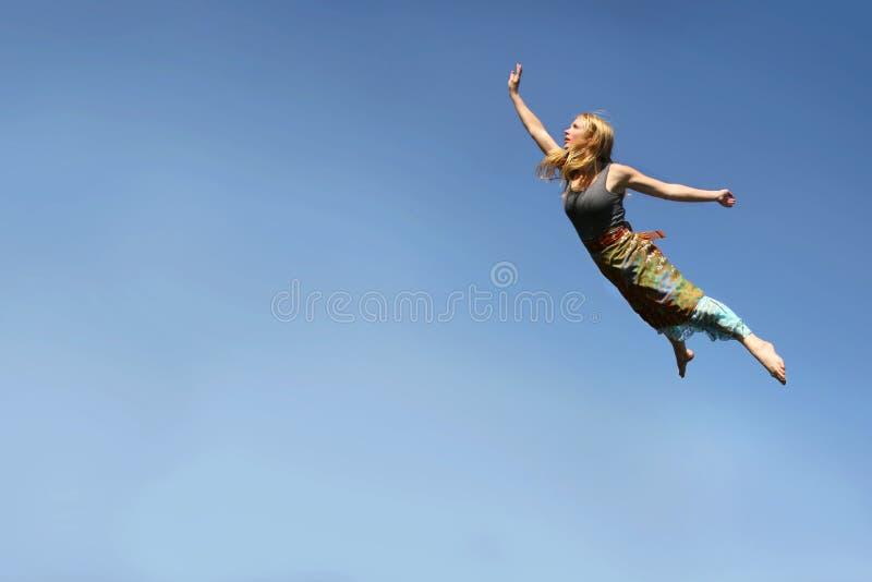 Voo da mulher através do céu azul imagens de stock