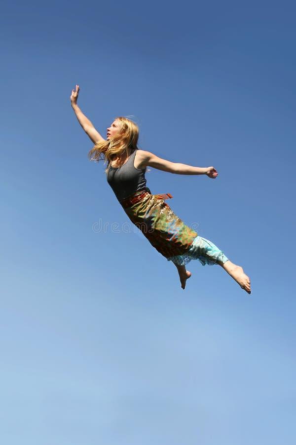 Voo da mulher através do céu azul foto de stock