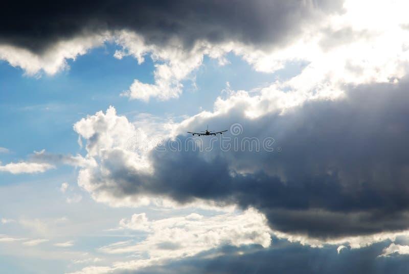 Voo da silhueta do avião ausente contra no céu dramático foto de stock