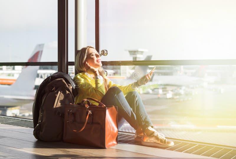 Voo de espera da menina do moderno no aeroporto e escuta a música imagem de stock