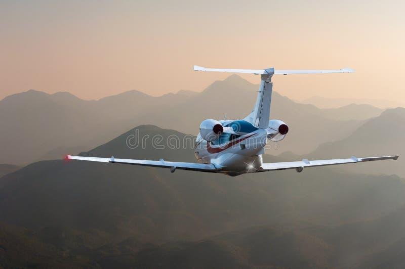Voo do avião acima da silhueta das montanhas altas no por do sol Conceito do curso e fundo das férias fotografia de stock royalty free