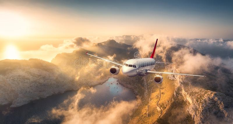 Voo do avião acima das montanhas e das baixas nuvens no por do sol foto de stock royalty free