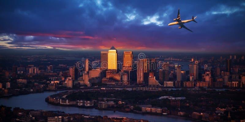 Voo do avião dos passageiros acima da cidade de Londres na luz do por do sol foto de stock royalty free