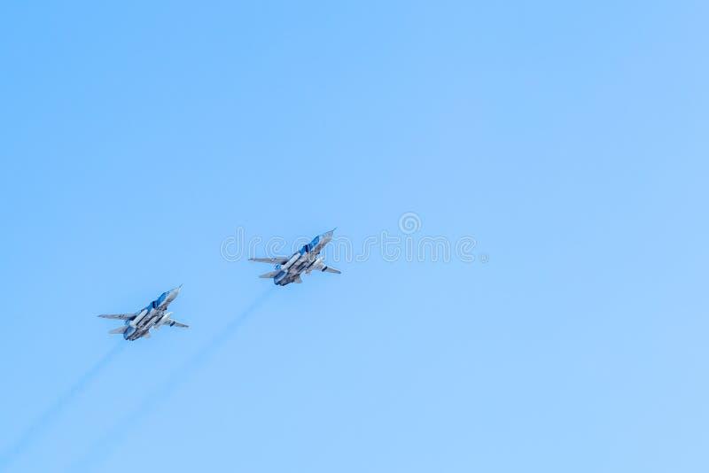 Voo do avião militar no céu azul um pares fotos de stock