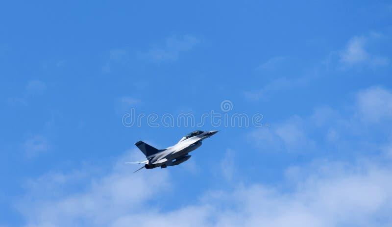 Voo do avião militar sobre o azul imagem de stock