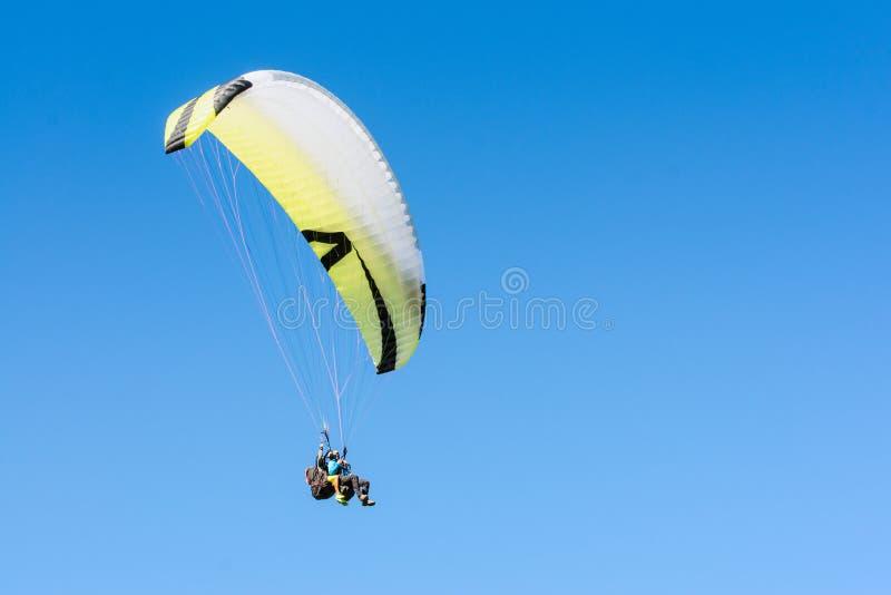 Voo do esporte do parapente na asa crescente no céu azul claro fotografia de stock