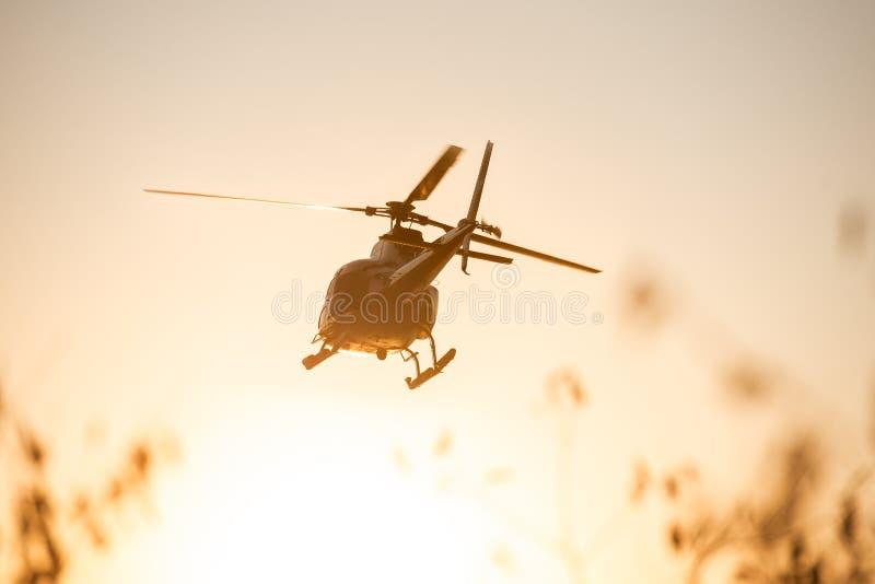 Voo do helicóptero do passageiro no céu do por do sol imagem de stock