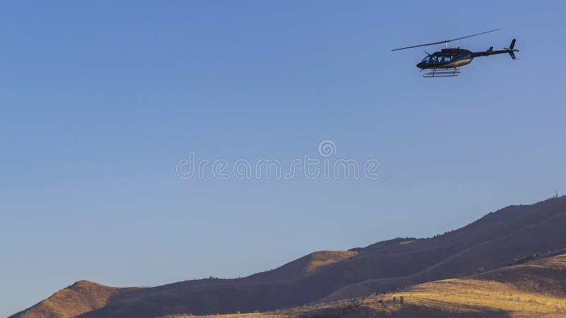 Voo do helic?ptero do quadro do panorama sobre uma montanha imensa com fundo claro do c?u azul imagens de stock royalty free