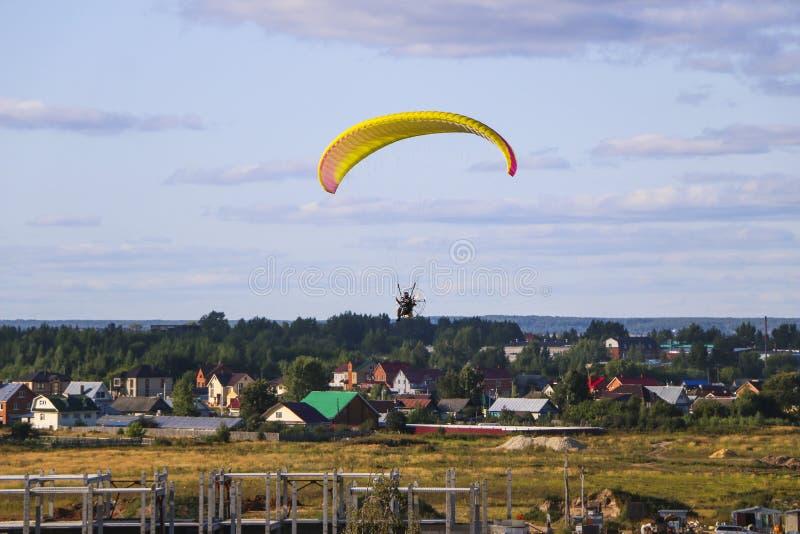 Voo do motor paraplan um homem voa em um motoparaplane colorido brilhante acima do canteiro da vila, do campo e das obras fotos de stock royalty free