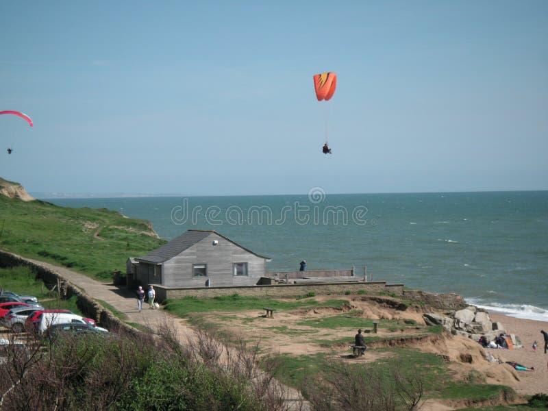 Voo do papagaio da foto que salta em queda livre sobre a baía ocidental Dorset fotografia de stock