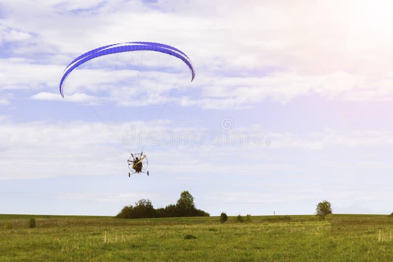 Voo do paraglider de Moto sobre um campo em um céu azul com nuvens imagens de stock royalty free