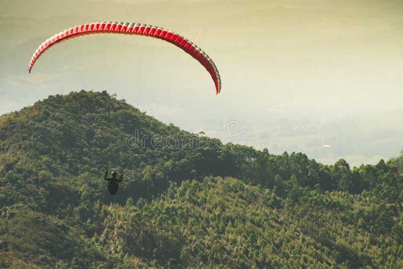 Voo do Paraglider no céu ensolarado bonito sobre as montanhas verdes em Poços de Caldas imagens de stock