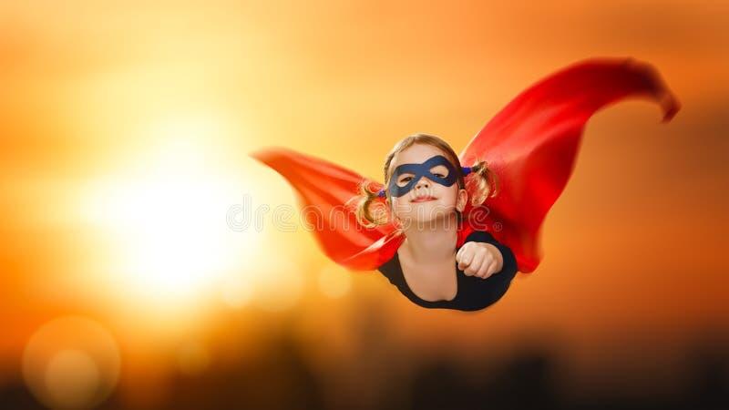 Voo do super-herói da menina da criança através do céu no por do sol fotos de stock royalty free