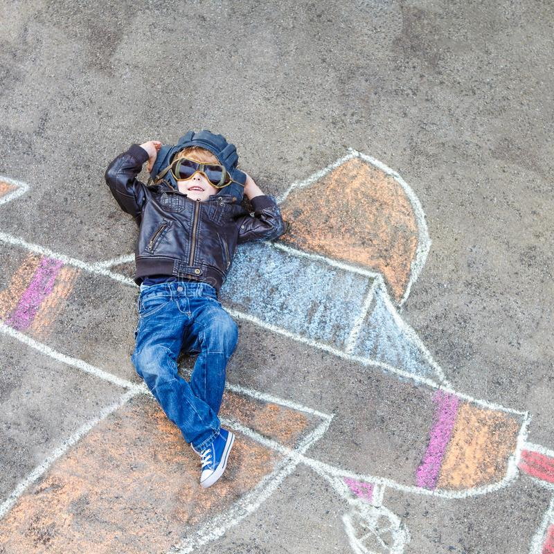 Voo engraçado do menino da criança por uma pintura plana da imagem com giz colorido Lazer criativo para crianças fora dentro imagens de stock royalty free