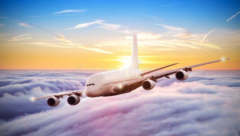 Voo enorme do avião acima das nuvens no por do sol dramático foto de stock