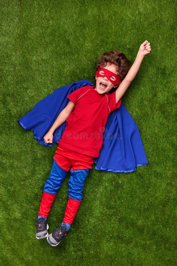 Voo entusiasmado do super-herói sobre o gramado foto de stock royalty free