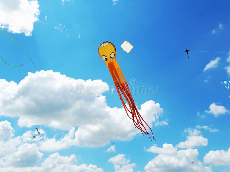 Voo grande do papagaio em um céu azul Papagaios de várias formas foto de stock