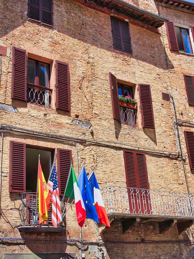 Voo internacional das bandeiras do balcão do prédio de apartamentos, Siena, Itália foto de stock
