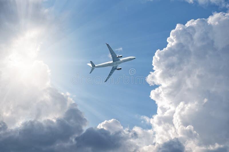 Voo no céu azul, altura do avião de ganho, brilho através das nuvens, vista inferior do sol fotos de stock royalty free