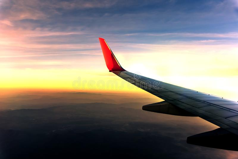 Voo no céu e nas nuvens na luz do sol com a floresta em montanhas como a janela completamente vista dos aviões fotos de stock royalty free