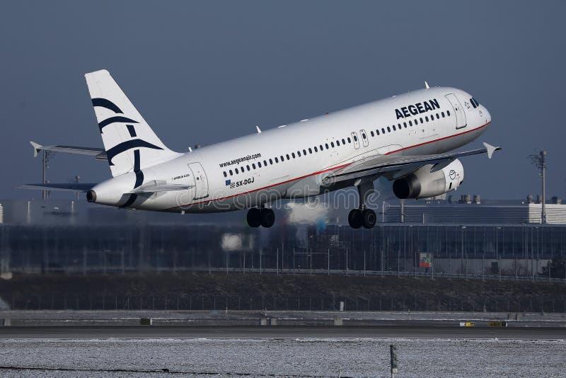 Voo plano aos destinos do feriado, neve das linhas aéreas egeias na pista de decolagem imagem de stock