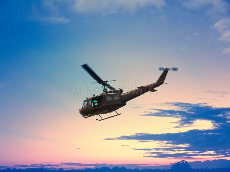 Voo preto do helicóptero no por do sol agradável com o céu azul vermelho e amarelo na montanha e na madeira da árvore imagem de stock