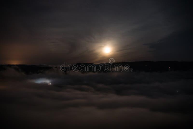 Voo sobre as nuvens de noite profunda com luz de lua Moon a aumentação sobre nuvens com luzes da cidade da noite Foto longa natur imagem de stock