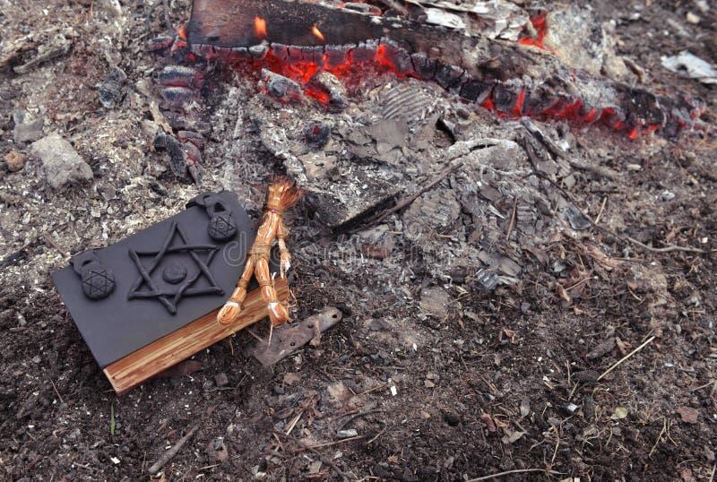 Voodoo кукла и книга черной магии в огне стоковые изображения