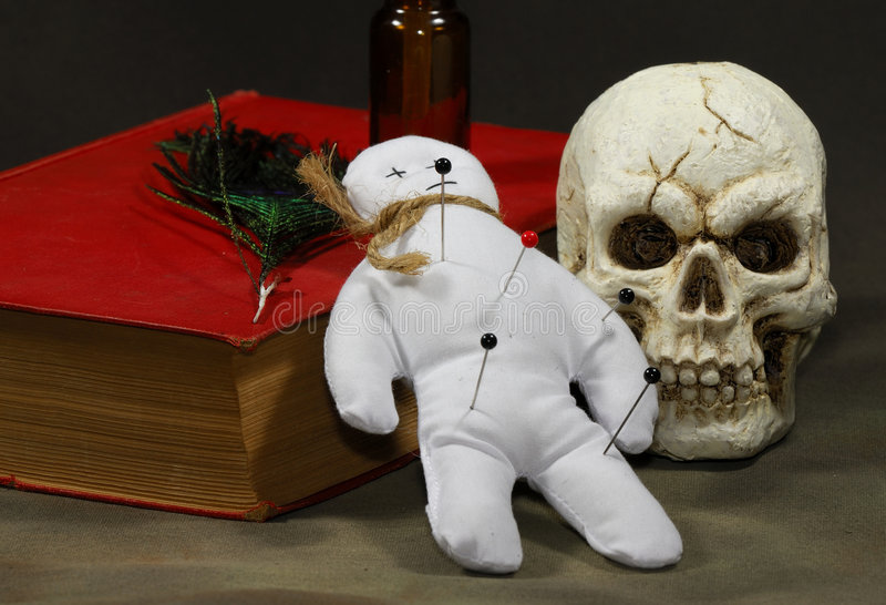 Voodoo. Doll with a Book and a Skull stock photography