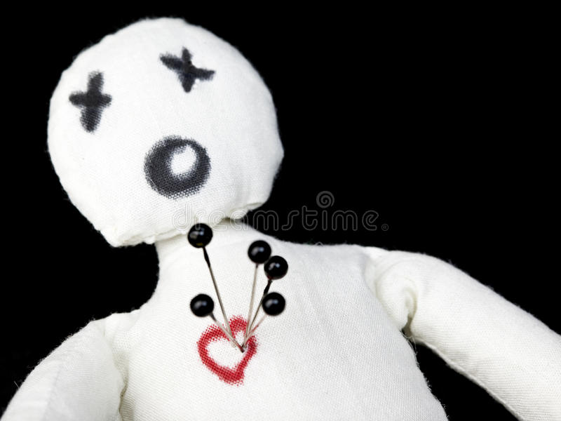 Voodoo Doll. White voodoo doll with pins in its heart photographed against a black background royalty free stock photography