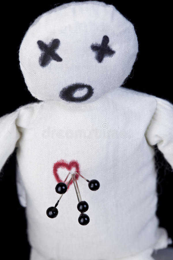 Voodoo Doll. White voodoo doll with pins in its heart photographed against a black background stock images