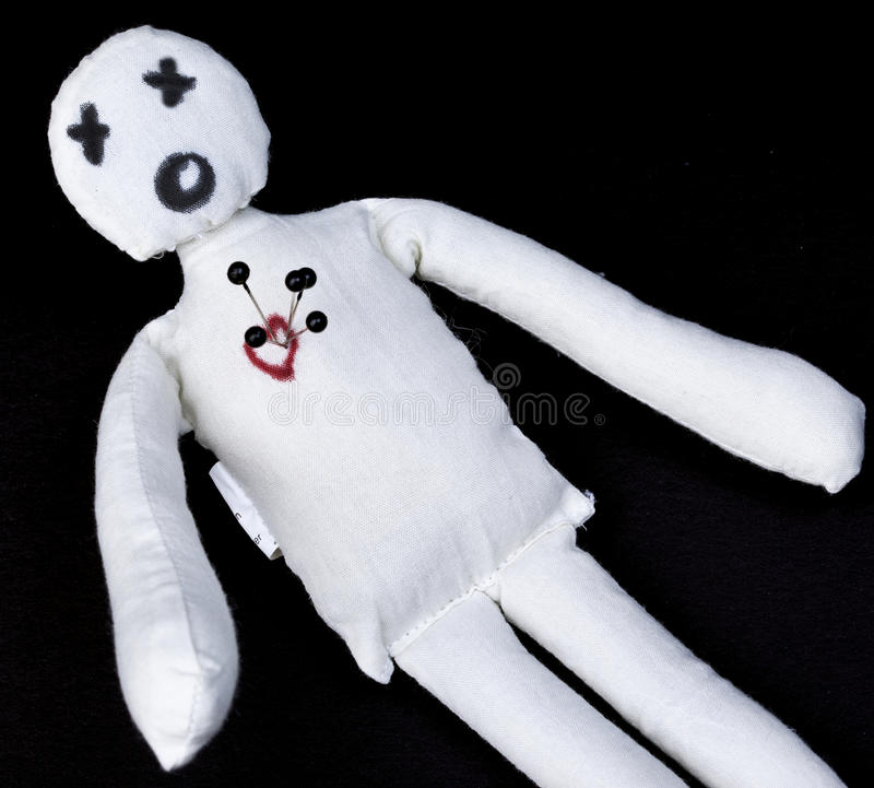 Voodoo Doll. White voodoo doll with pins in its heart photographed against a black background royalty free stock images