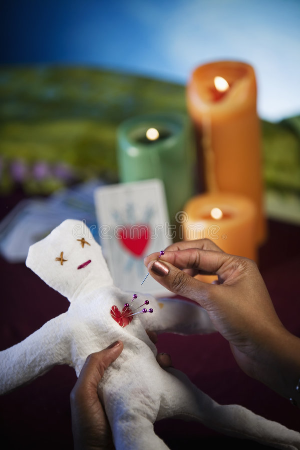 Voodoo Doll. Held by and African American woman sticking pins in its heart royalty free stock photo