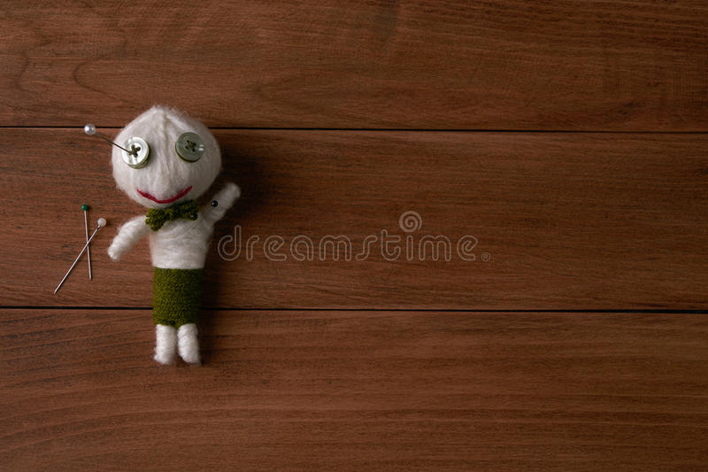 Voodoo Doll. Cute Little Voodoo Doll with pins on wooden background.Copy space royalty free stock photography