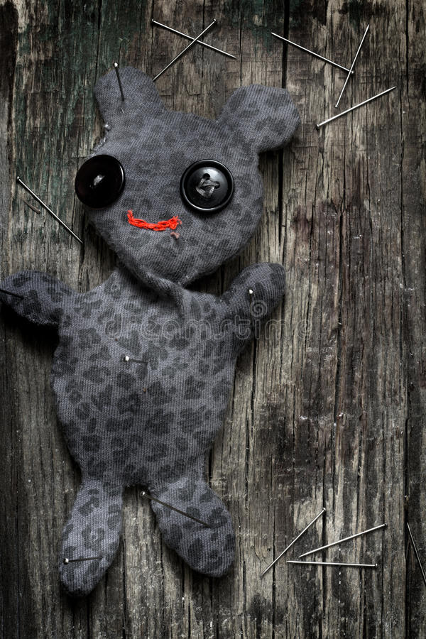 Voodoo doll and pins on old vintage wooden floor stock photos