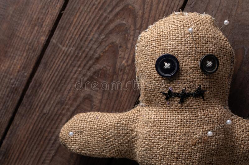 Voodoo doll on a wooden background with dramatic lighting. The concept of witchcraft and black art. Burlap doll on a wooden royalty free stock image